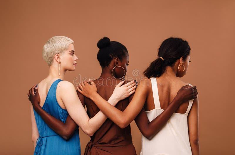 Três mulheres diversas que estão contra o fundo marrom imagem de stock