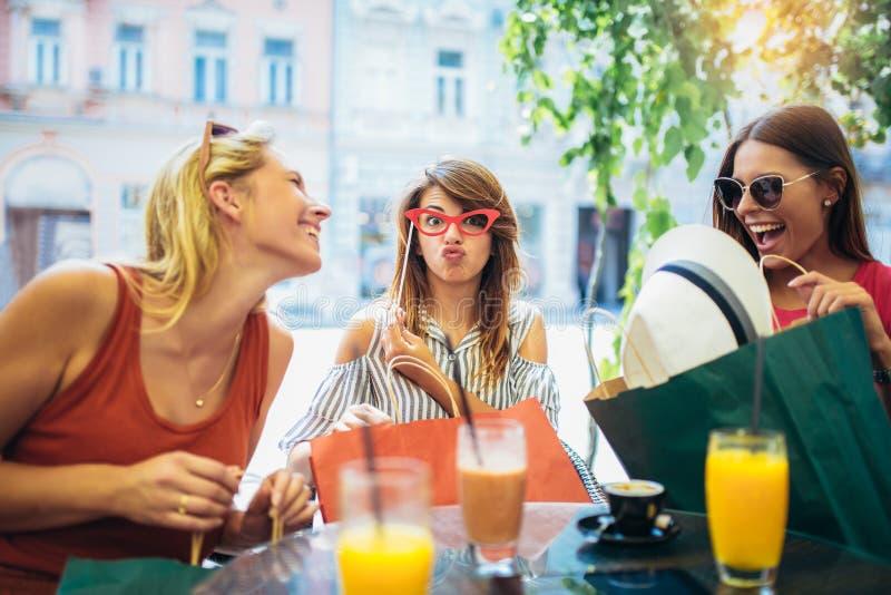 Três mulheres em um café após uma compra imagens de stock
