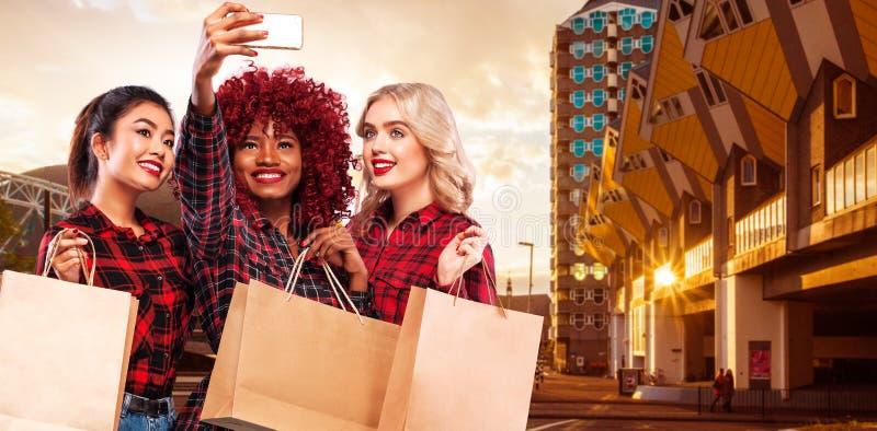 Três mulheres felizes na compra Raças do afro-americano, do asiático e do caucasian Feriado de Black Friday Conceito para vendas  fotos de stock royalty free