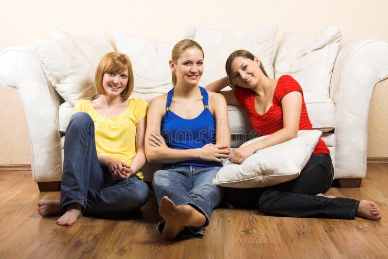 Três mulheres felizes na sala de visitas imagens de stock royalty free