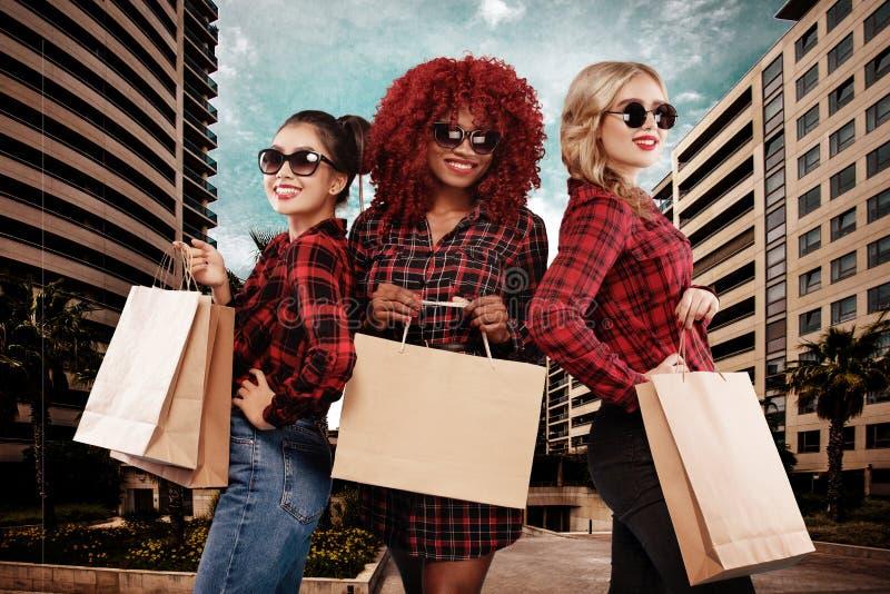 Três mulheres felizes nos óculos de sol Raças do afro-americano, do asiático e do caucasian Compra no feriado preto de sexta-feir foto de stock