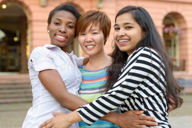 Três mulheres multiculturais que abraçam-se fotos de stock royalty free