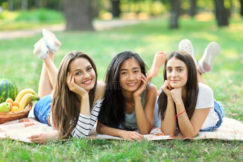 Três mulheres multirraciais felizes novas que encontram-se na grama no parque imagens de stock royalty free