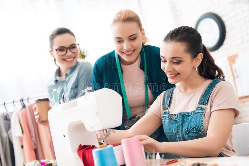 Três mulheres na fábrica do vestuário Um deles está costurando o vestido novo imagem de stock