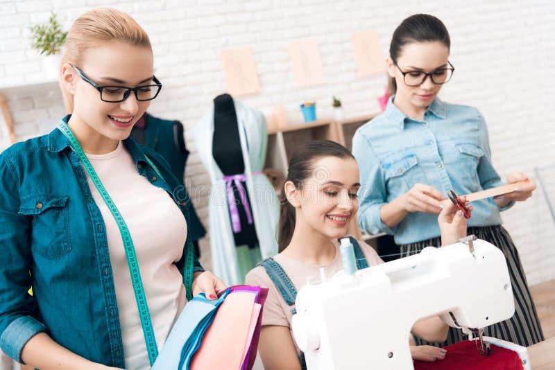 Três mulheres na fábrica do vestuário Um deles está sentando-se atrás da máquina de costura fotos de stock royalty free