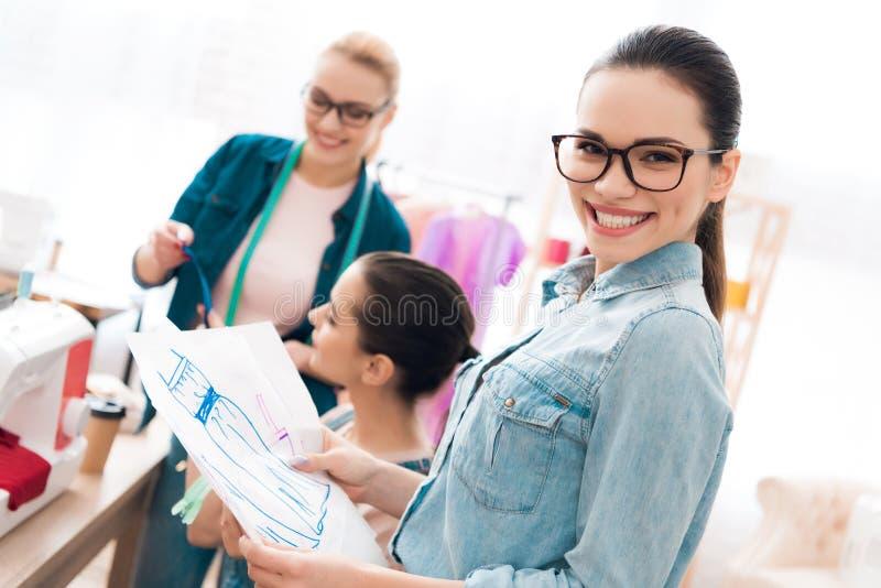 Três mulheres na fábrica do vestuário Um deles está sentando-se atrás da máquina de costura imagens de stock royalty free