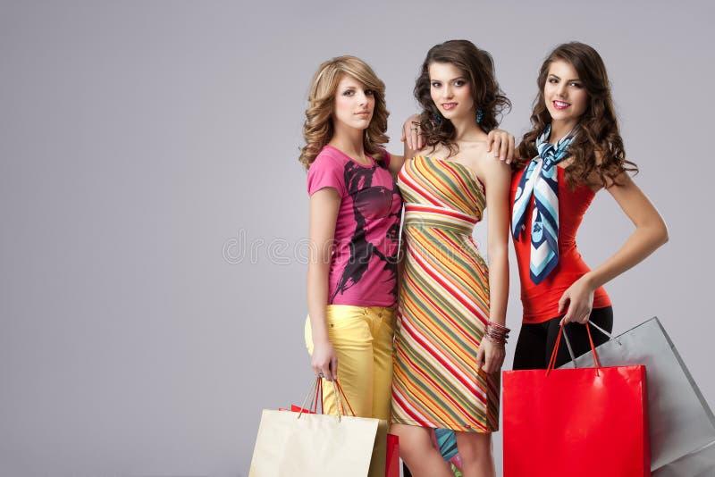 Três mulheres novas bonitas que prendem sacos de compra fotografia de stock