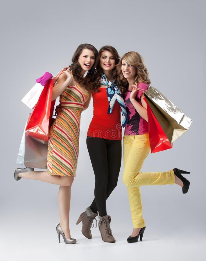 Três mulheres novas bonitas que prendem sacos de compra imagens de stock royalty free