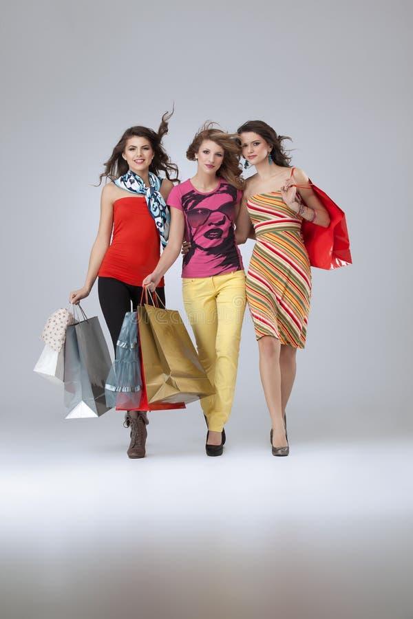 Três mulheres novas bonitas que prendem sacos de compra imagem de stock