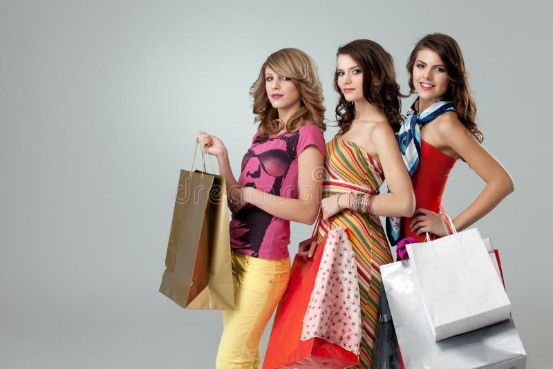 Três mulheres novas bonitas que prendem sacos de compra fotografia de stock royalty free