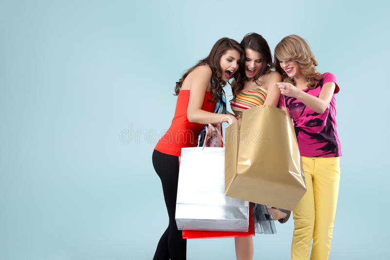 Três mulheres novas bonitas que prendem sacos de compra imagens de stock