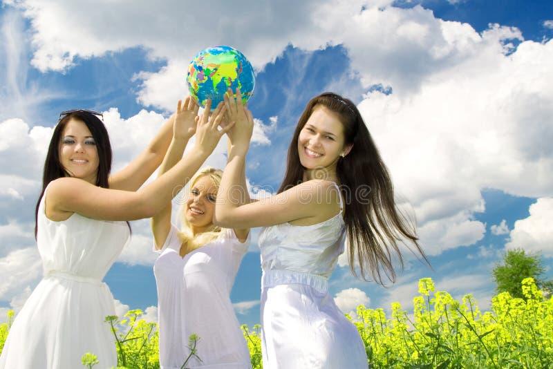 Três mulheres novas com globo imagem de stock