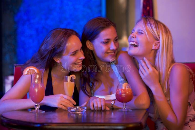 Três mulheres novas que sentam-se em uma tabela e em um riso foto de stock royalty free