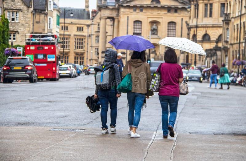 Três mulheres que andam afastado com guarda-chuvas e sacos em um dia chuvoso em Oxford Inglaterra foto de stock royalty free