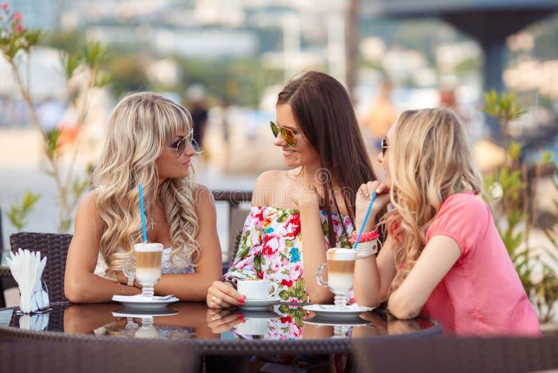 Três mulheres que apreciam a xícara de café no café imagem de stock royalty free