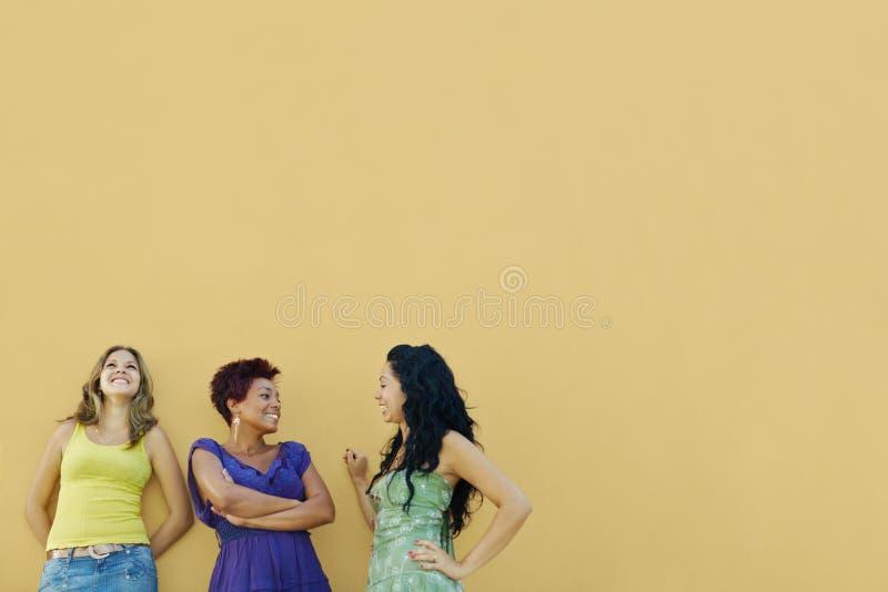 Três mulheres que falam e que têm o divertimento imagens de stock