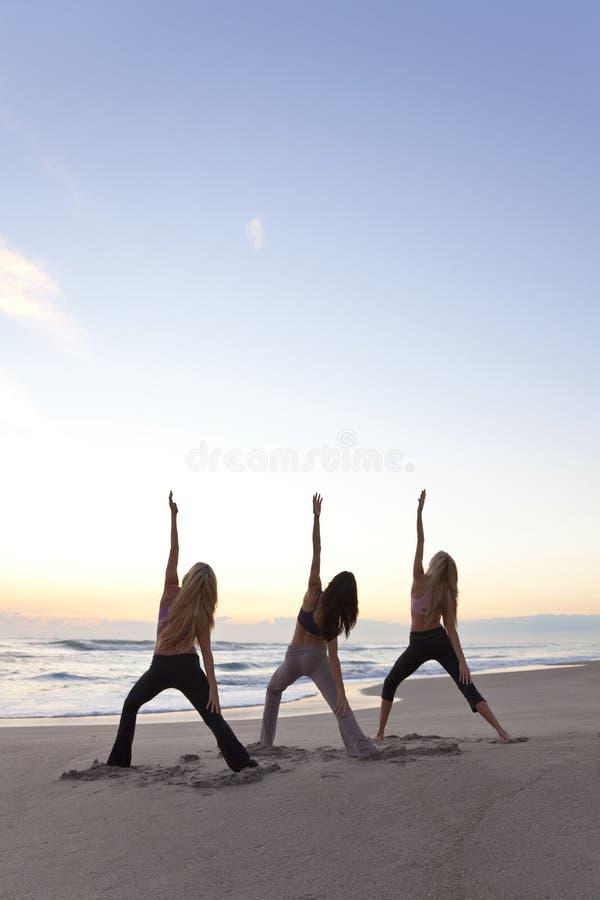 Três mulheres que praticam a ioga na praia no nascer do sol fotografia de stock royalty free