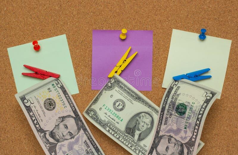 Três notas coloridas com percevejos e pregadores de roupa com os dólares isolados em um fundo da cortiça imagens de stock