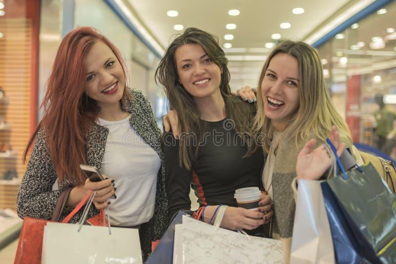 Três novos e as meninas bonitas estão guardando os sacos de compras e o g imagem de stock