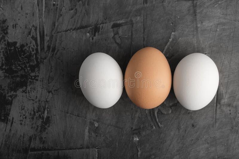 Três ovos, dois brancos e um marrom em um fundo preto imagem de stock royalty free