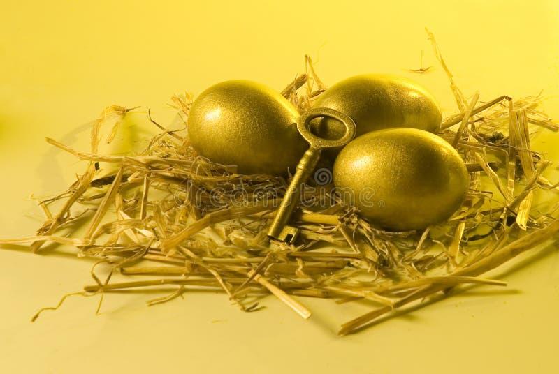 Três ovos dourados e uma chave que encontra-se na palha fotografia de stock