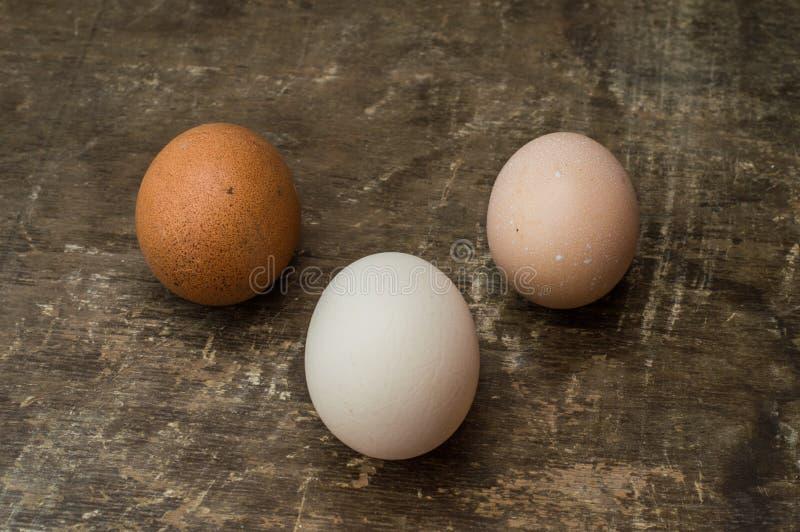 Três ovos frescos da galinha em um fundo de madeira velho fotos de stock royalty free