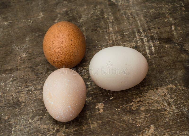 Três ovos frescos da galinha em um fundo de madeira velho fotos de stock