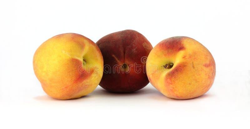 Três pêssegos coloridos fotos de stock
