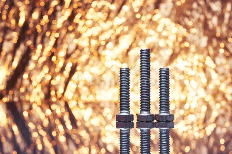 Três parafusos do metal com fundo brilhante extravagante do ouro completamente das faíscas fora de foco imagem de stock royalty free