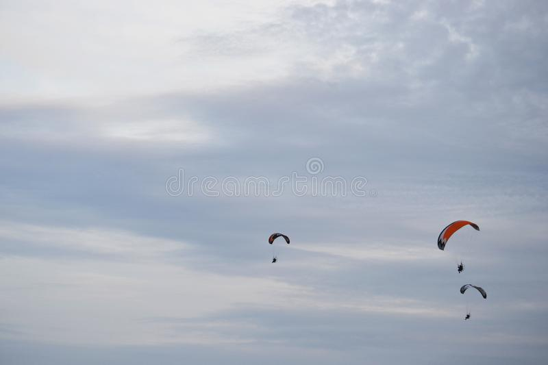 Três paragliders que voam longe em um céu nebuloso claro no verão fotografia de stock royalty free