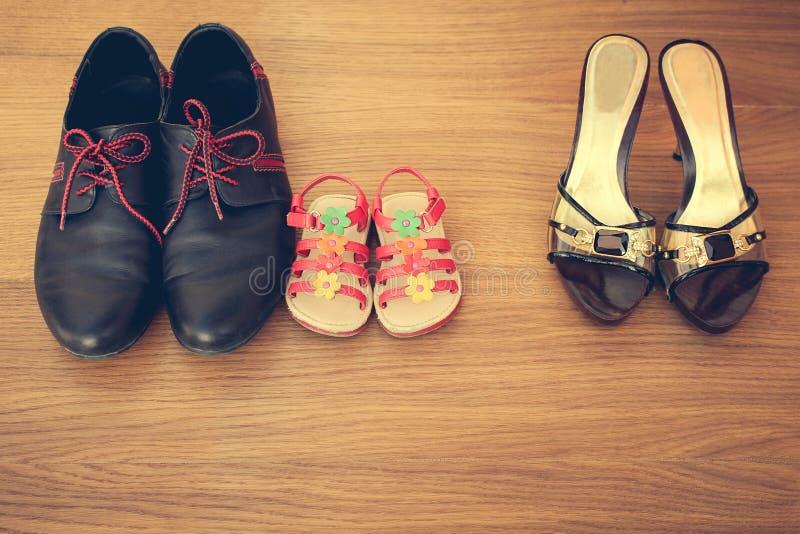 Três pares de sapatas: homens, mulheres e crianças fotos de stock royalty free