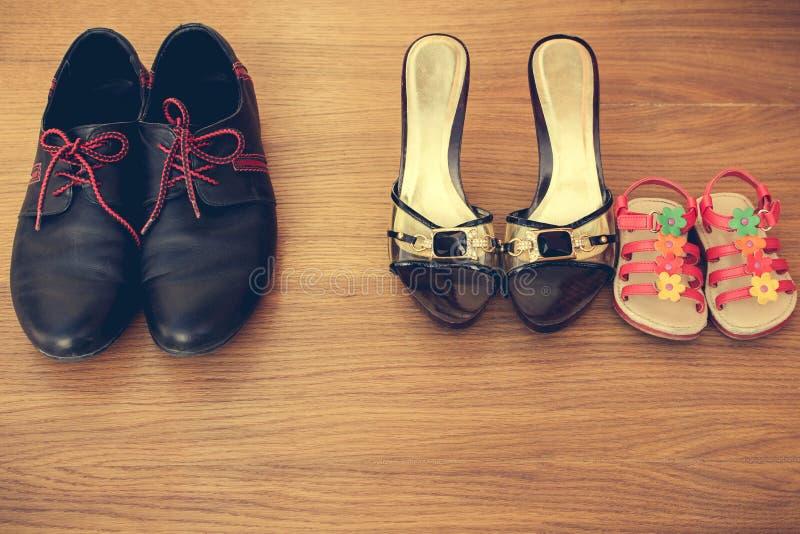 Três pares de sapatas: homens, mulheres e crianças Suporte das sandálias do bebê ao lado das sapatas das mulheres foto de stock