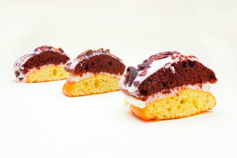 Três partes de biscoito delicioso endurecem, os queques brancas e marrons do cacau cobertos com chocolate branco Doce caseiro um  foto de stock