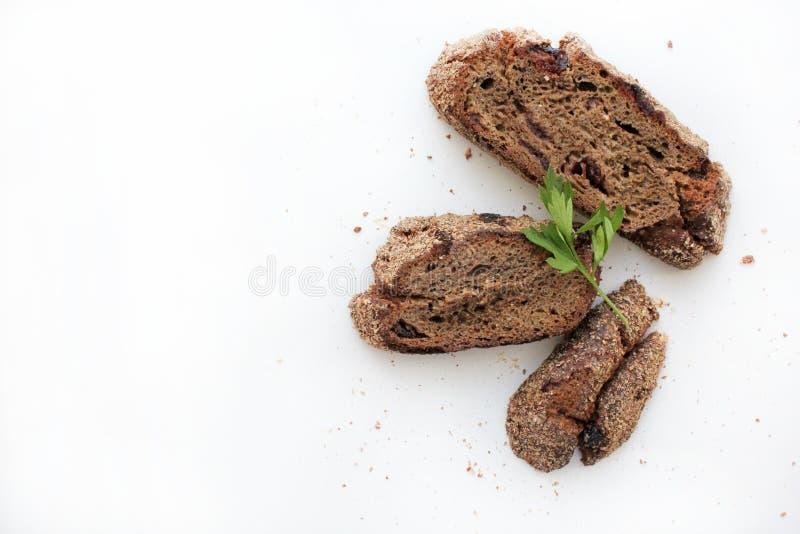 Três partes de pão de centeio e de um ramo da salsa em um fundo branco imagem de stock