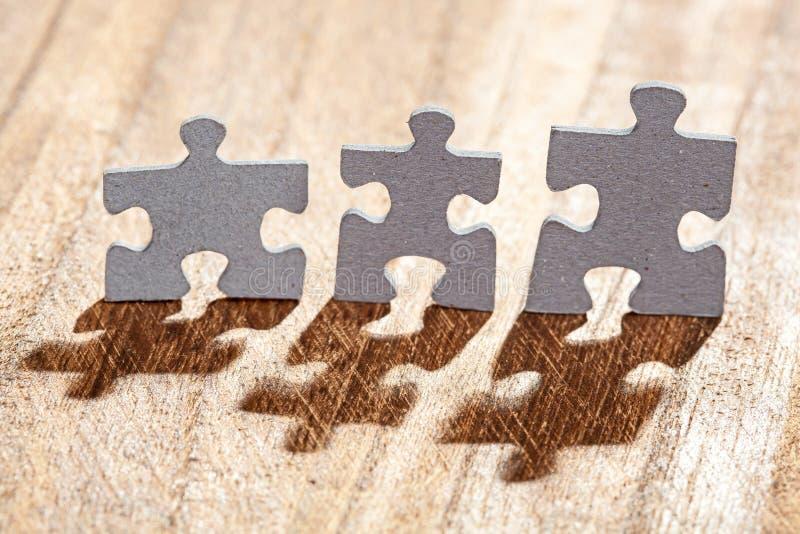Três partes do enigma de serra de vaivém no Lit da tabela pela luz traseira fotos de stock royalty free