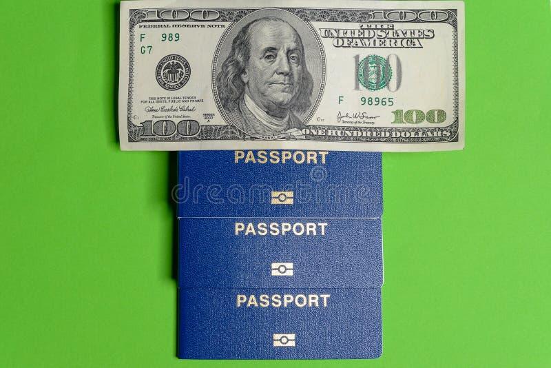 Três passaportes biométricos azuis com cem denominações do dólar fotografia de stock