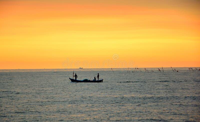Três pescadores em um barco de pesca pequeno fotos de stock royalty free
