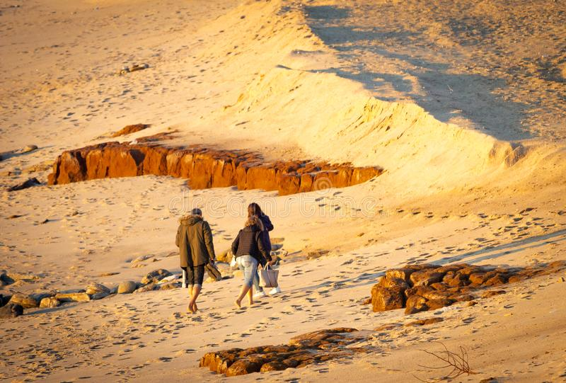 Três pessoas andam na praia foto de stock