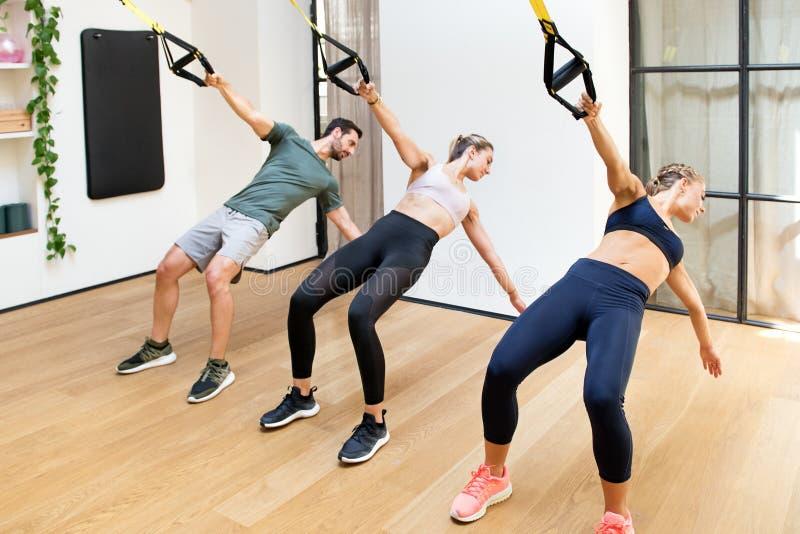 Três pessoas que treinam a tração do poder com trx no gym fotografia de stock