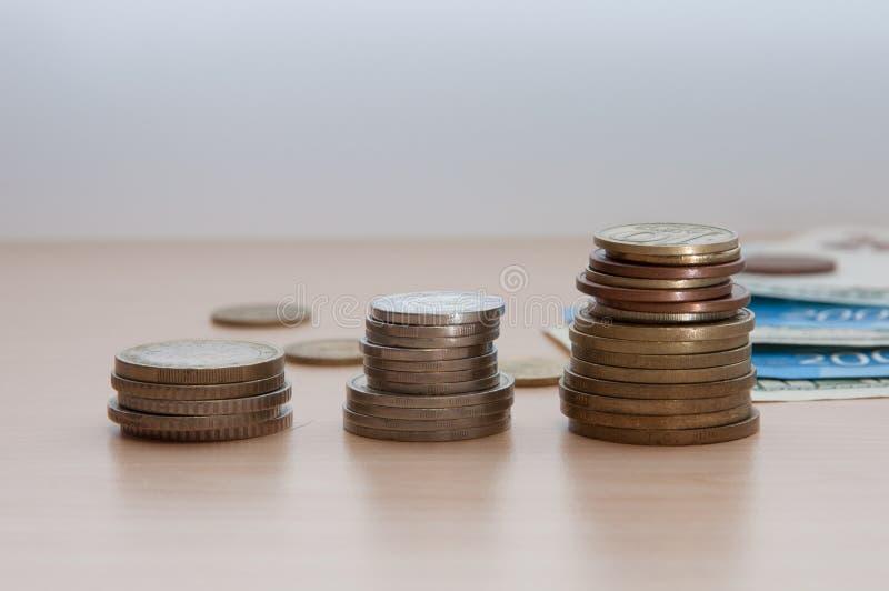 Três pilhas de moedas e de contas encontram-se na tabela imagem de stock royalty free
