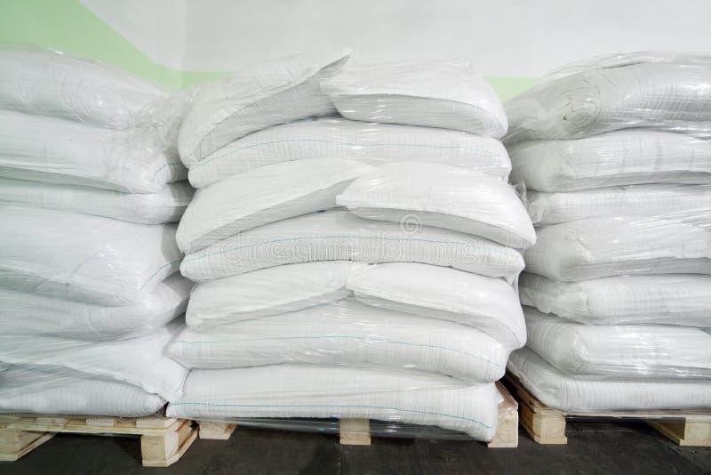 Três pilhas de sacos brancos grandes no grande armazém fotografia de stock