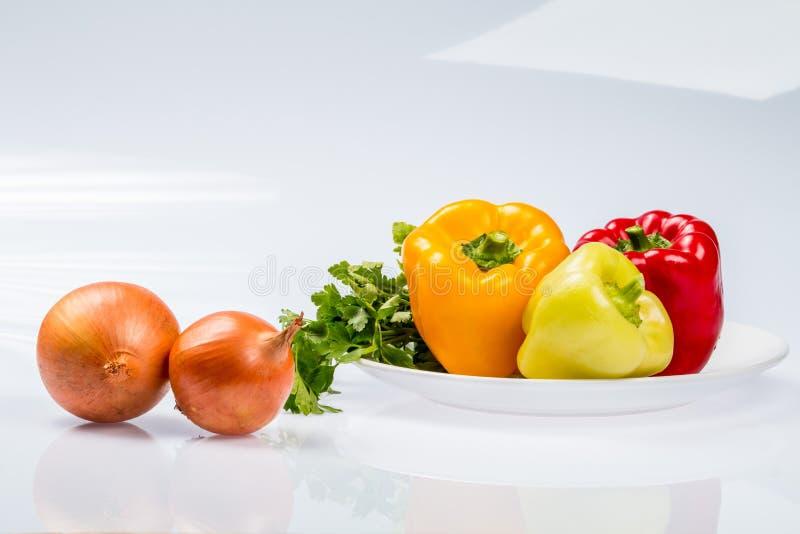 Três pimentas búlgaras maduras deliciosas, cal, vermelho, laranja, e duas cebolas em uma placa, em um fundo branco fotos de stock