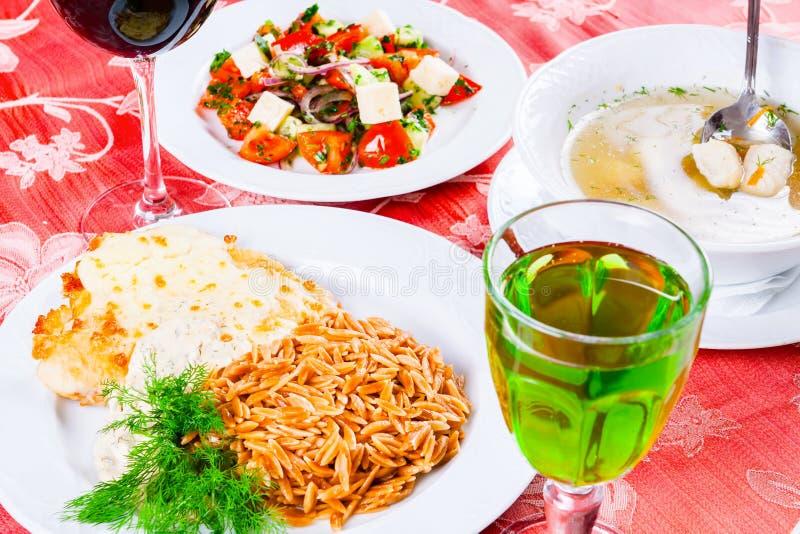Três placas com os pratos do almoço na tabela A salada, a sopa dos peixes e a costeleta de carneiro vegetais da galinha com solet foto de stock royalty free