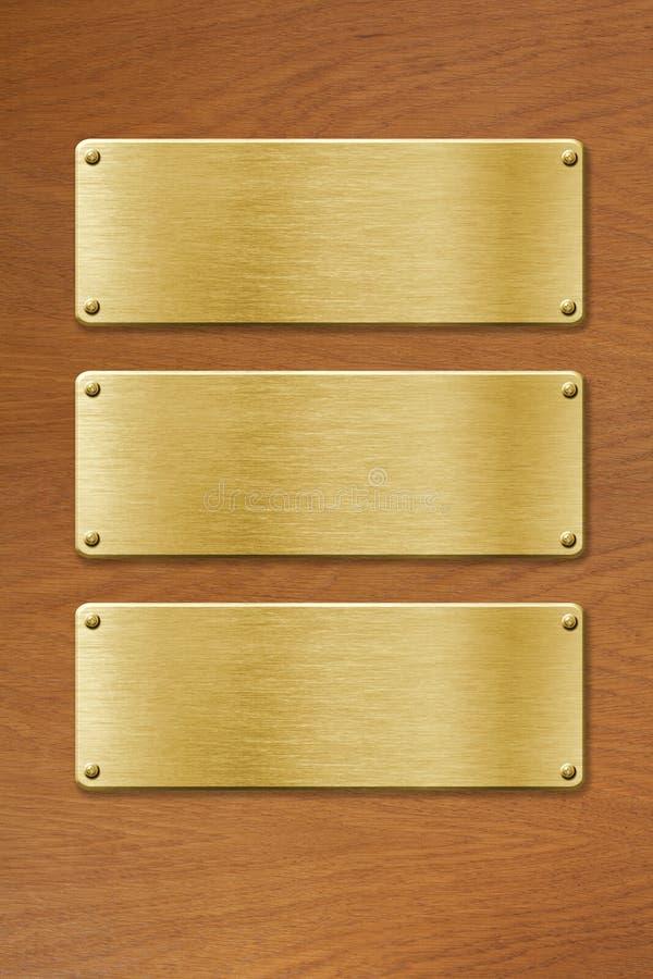 Três placas de metal douradas sobre o fundo de madeira da textura imagem de stock royalty free