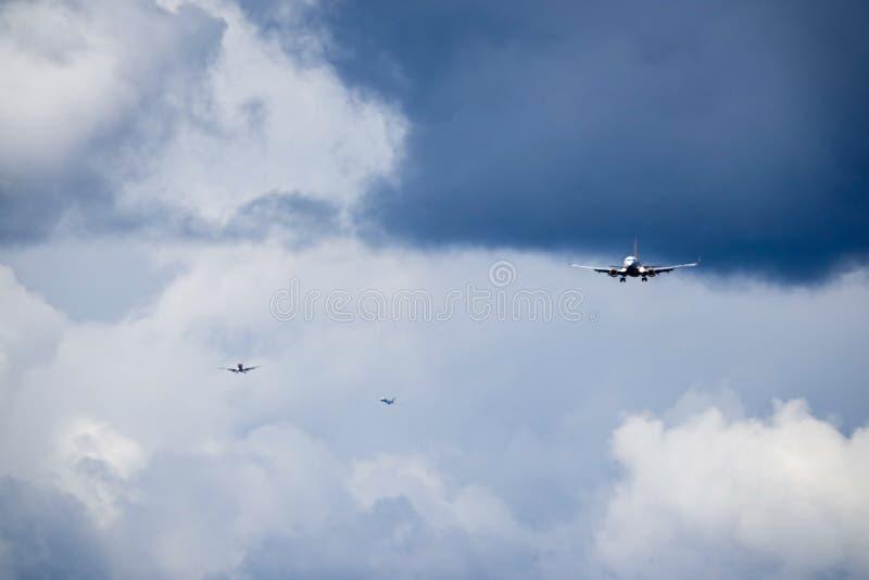 Três planos de jato/aviões entram na pista de decolagem da aterrissagem em um aeroporto fotografia de stock royalty free