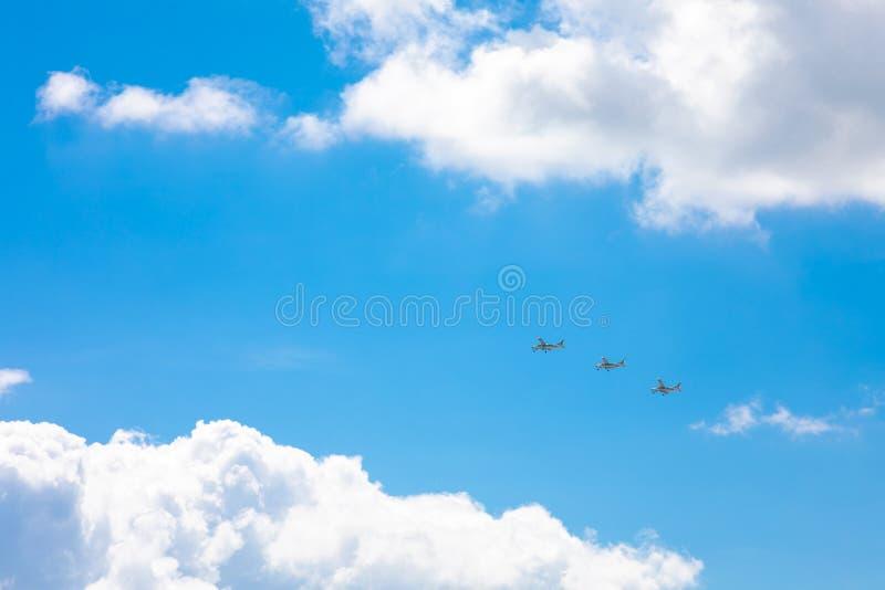 Três planos que voam no céu azul, cercado por nuvens e por luz solar fotos de stock royalty free