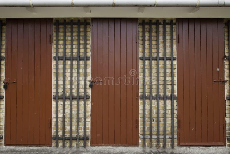 Três portas de madeira vermelhas na parede de tijolo amarela fotos de stock royalty free