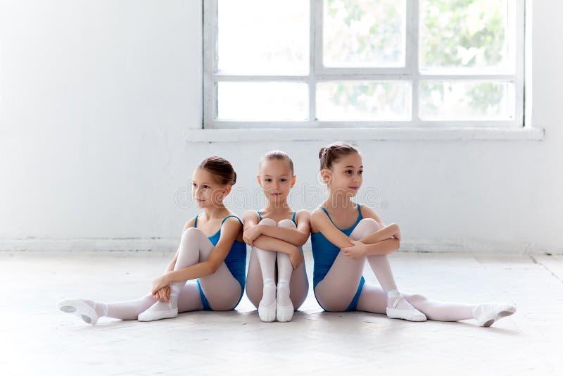 Três poucas meninas do bailado que sentam-se e que levantam junto foto de stock