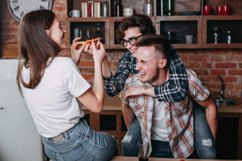 Três povos alegres novos que comem a pizza fotografia de stock