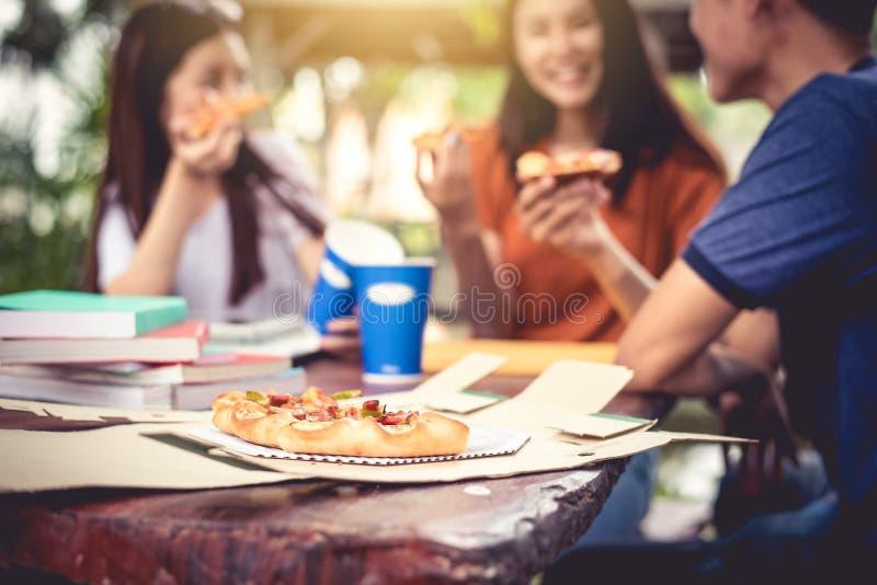 Três povos asiáticos apreciam comer a pizza no ar livre após o tutoria fotografia de stock royalty free